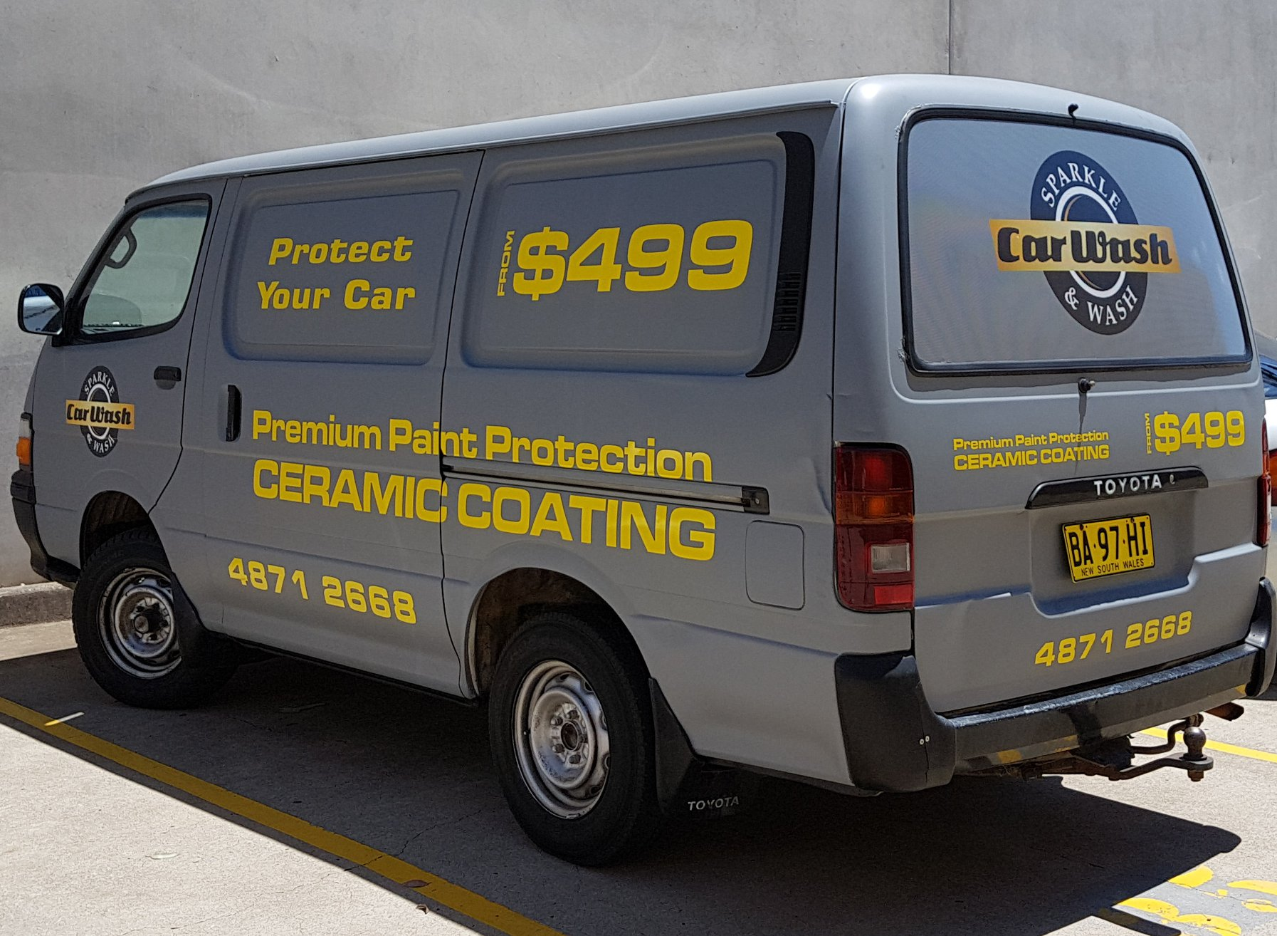 Grey Toyota Hiace with yellow sign writing, done with vinyl cut lettering and clearview.